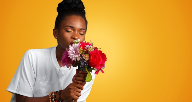Beautiful african woman with fresh colorful flowers