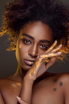 彼女の顔と体に金の輝きを持つナチュラルメイクの美しいアフリカの女性。