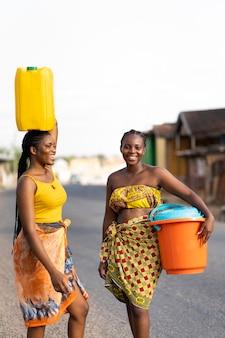 야외에서 물을 가져 오는 아름 다운 아프리카 여성