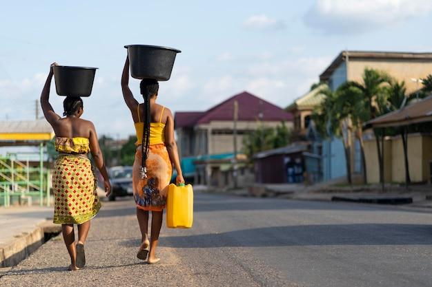 Beautiful african women fetching water from outside