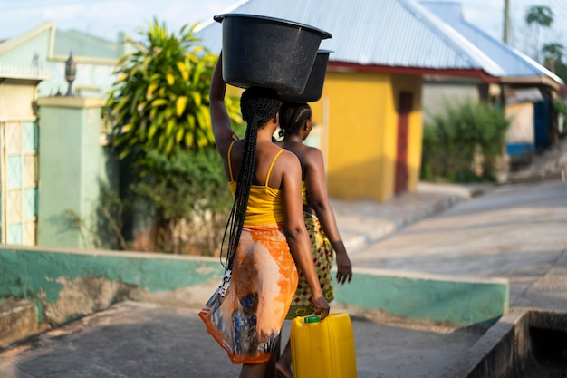 외부에서 물을 가져 오는 아름다운 아프리카 여성