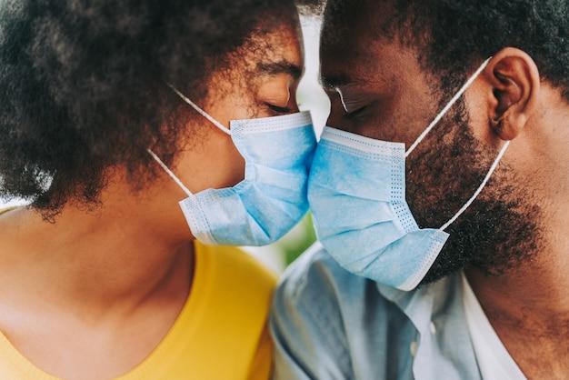 Covid-19パンデミック検疫中に抱きしめ、保護フェイスマスクを身に着けている自宅で美しいアフリカ系アメリカ人のカップル