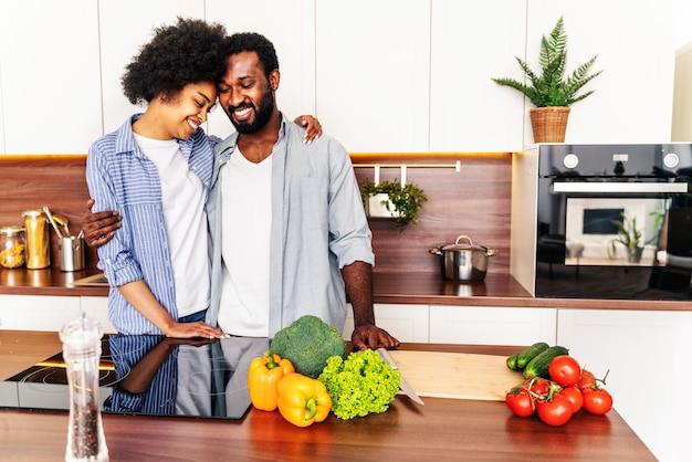 집에서 요리하는 아름다운 아프리카계 미국인 부부 - 부엌에서 함께 저녁 식사를 준비하는 아름답고 쾌활한 흑인 부부