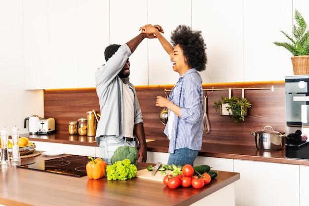집에서 요리하는 아름다운 아프리카 계 미국인 부부 저녁 식사를 준비하는 아름답고 쾌활한 흑인 부부