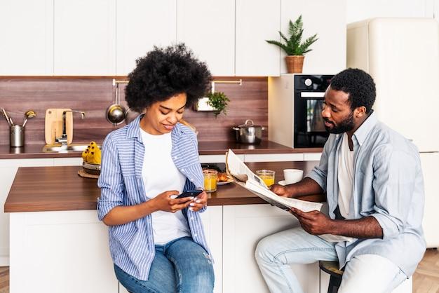 집에서 함께 아침 식사를 하는 아름다운 아프리카계 미국인 부부 - 아침에 함께 시간을 보내는 쾌활한 흑인 부부