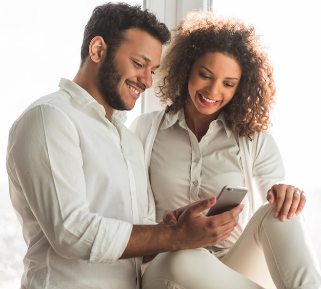 Beautiful afro american couple is using a smartphone.