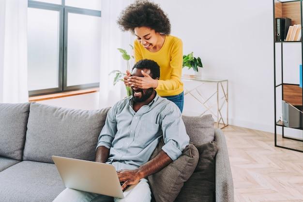 Красивая афро-американская пара, работающая на портативном компьютере - современная пара, делающая покупки в интернете