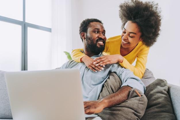 コンピューターのラップトップデバイスで作業している美しいアフリカ系アメリカ人のカップル-オンラインショッピングの現代のカップル