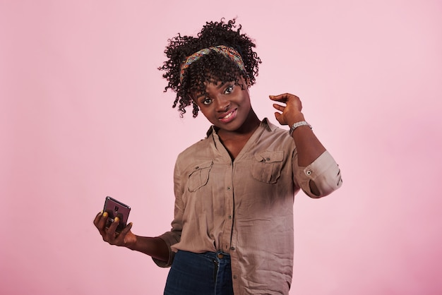 Beautiful afro american girl stands in the studio with pink background and holds phone
