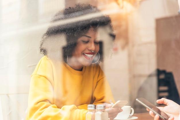 コーヒーショップで携帯電話を使用して美しいアフリカ系アメリカ人の女性。コミュニケーションの概念。