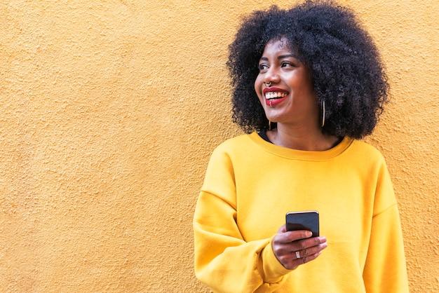 通りで携帯電話を使用して美しいアフリカ系アメリカ人の女性。コミュニケーションの概念。