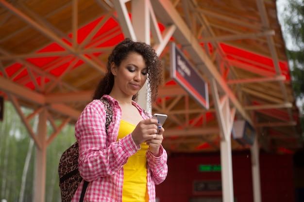 Красивая афро-американская женщина с помощью мобильного телефона на улице. связь