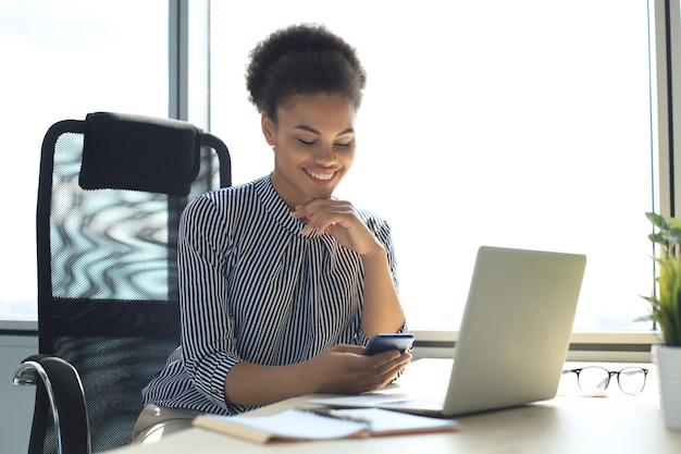 Красивая афро-американская женщина с помощью мобильного телефона и ноутбука. концепция коммуникации.