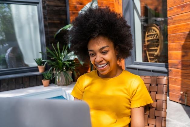 自宅で巻き毛を持つ美しいアフリカ系アメリカ人の女性