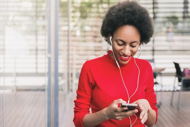 スマートフォンを介してオンライン音楽を聴くイヤホンを着て美しいアフロ黒人女性