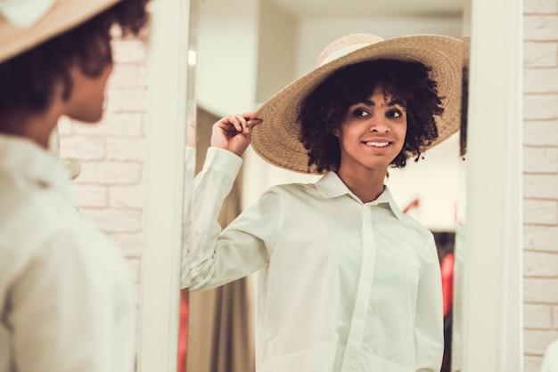 Beautiful afro girl is fitting on stylish straw hat.