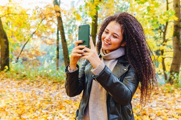 Красивая афро-волосатая женщина прогулки в осеннем парке в солнечный теплый день. портрет женщины на открытом воздухе, делающей фотографии со смартфоном