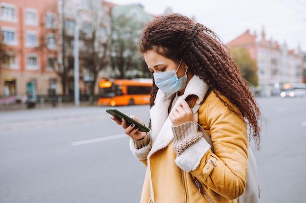 保護医療用フェイスマスクを身に着けている美しいアフロヘアーの女性が通りに立って、スマートフォンでメッセージをテキストメッセージで送信します。