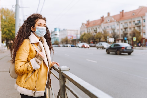 Beautiful afro haired woman wearing protective medical face mask stand on the street of city. social distancing, quarantine.