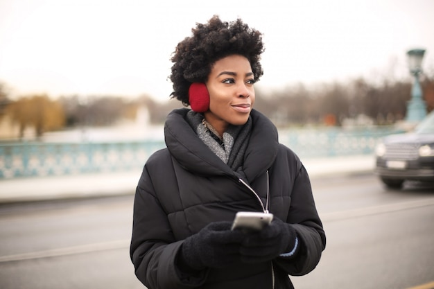 Beautiful afro woman listening to music on headphones in the city