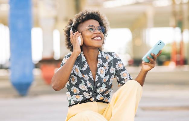 美しいアフロの女性は非常に幸せに彼女の携帯電話からヘッドフォンで音楽を聴きます