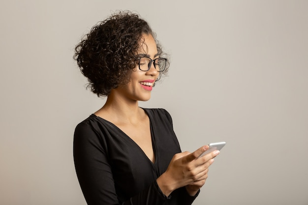 Beautiful afro woman smiling, wearing glasses and using smartphone