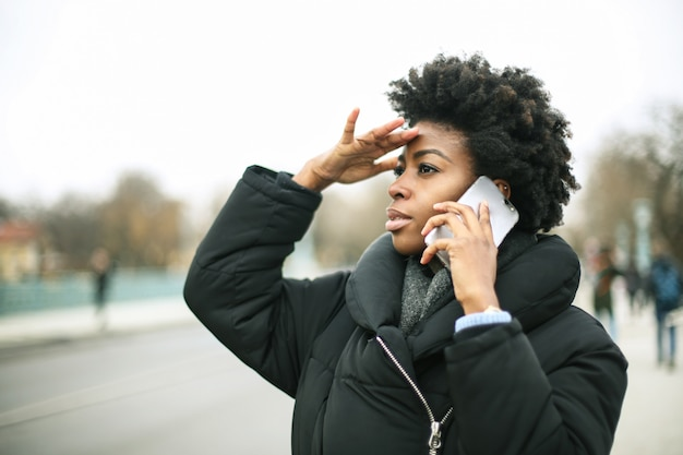 Beautiful afro woman talking on a smartphone outdoor