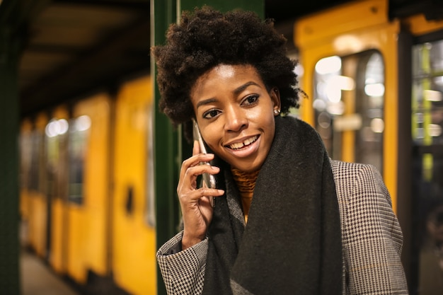 Beautiful afro woman talking on the smartphone in the subway