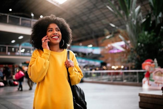 駅で携帯を使っている美しいアフロ女性。コミュニケーションの概念。