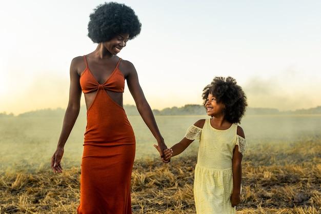 ひまわり畑でおしゃべりして楽しんでいる美しいアフリカ系アメリカ人のお母さんと娘