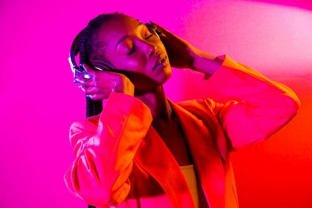 アフロピグテールの髪型とスタイリッシュな服を着た美しいアフリカ系アメリカ人の女性