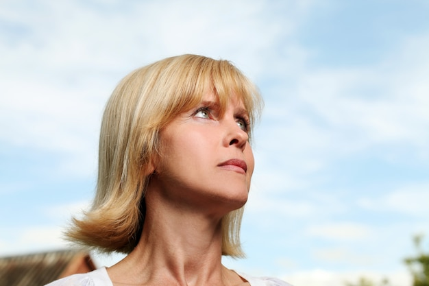 Beautiful aged woman over sky background