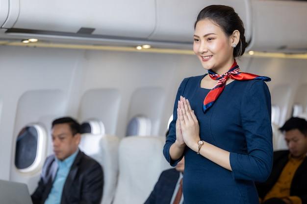 Beautiful air hostess in an airplane smiling, portrait of asian air hostess posing sawasdee, cabin crew or air hostess working in airplane.