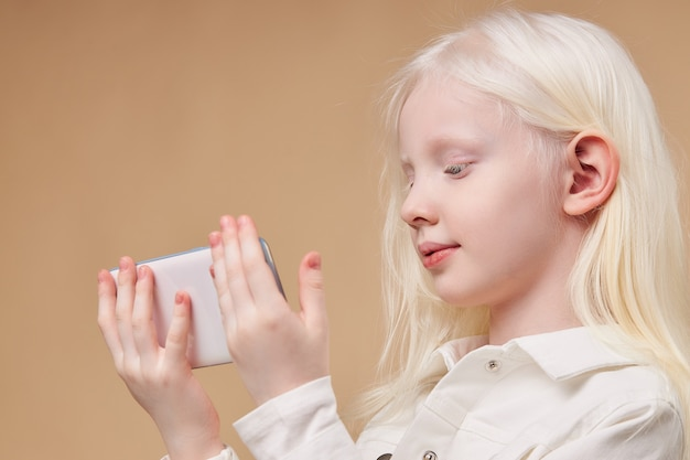 Beautiful albino child holding white smartphone in hands isolated