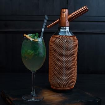 Красивый алкогольный коктейль в элегантном бокале с добавлением текилы и свежих листьев мяты стоит на винтажном столе в ресторане возле роскошной золотой бутылки. экзотический напиток
