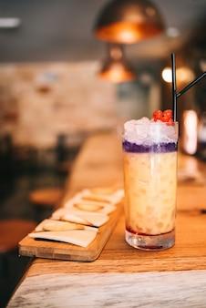 木製のバーカウンターとチーズスナックの美しいアルコールカクテル