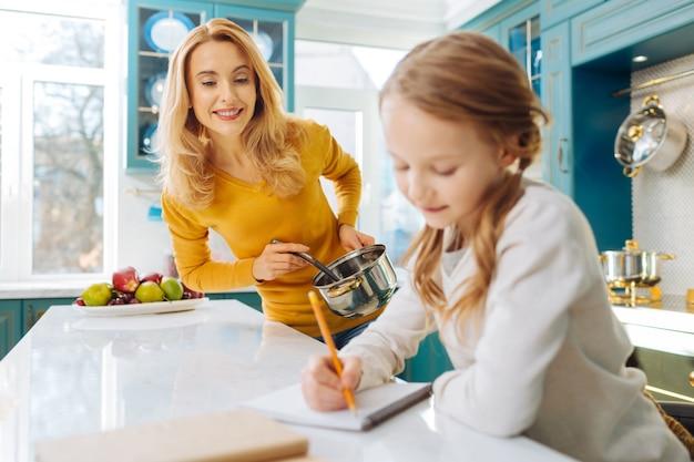 Красивая бдительная блондинка молодая мать улыбается и держит кастрюлю, глядя на свою маленькую дочь, пишущую в своем блокноте