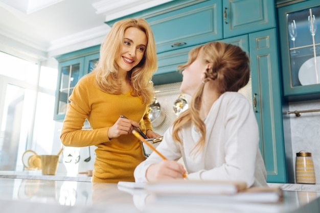 Красивая бдительная блондинка молодая мать улыбается и держит кастрюлю, глядя на свою маленькую дочь