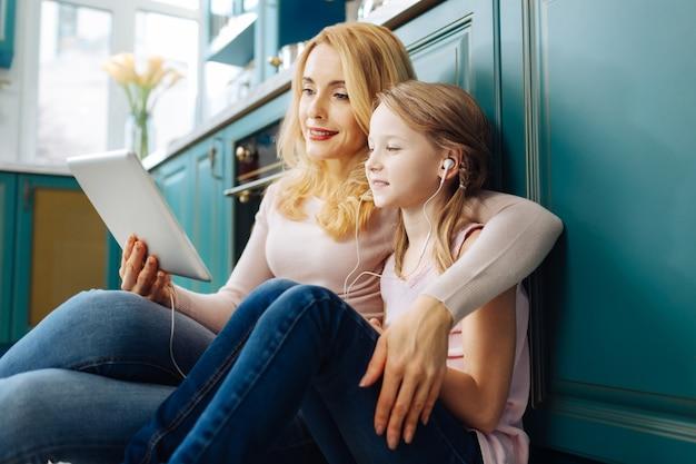 Красивые бдительные светловолосые мать и дочь улыбаются и сидят на полу на кухне и слушают музыку