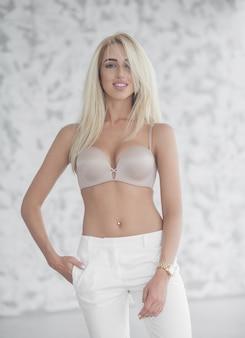 화이트 룸에서 포즈 베이지 색 란제리와 흰색 청바지에 아름 다운 매혹적인 젊은 여자