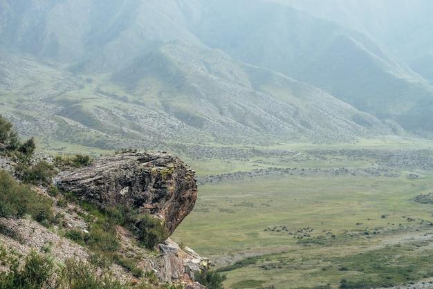 緑の山腹を背景に崖の端近くの山に大きな石の棚と美しい高山の風景。緑の山の谷の上の丘に岩の棚がある大気の山の風景。