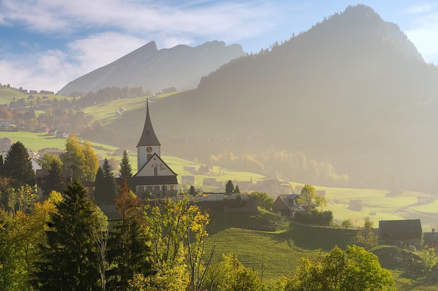 スイス連邦共和国、秋の晴れた日の教会の美しい高山風景。