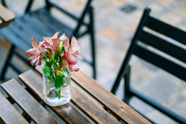 Beautiful alstroemeria in vase on wooden table in summer cafe