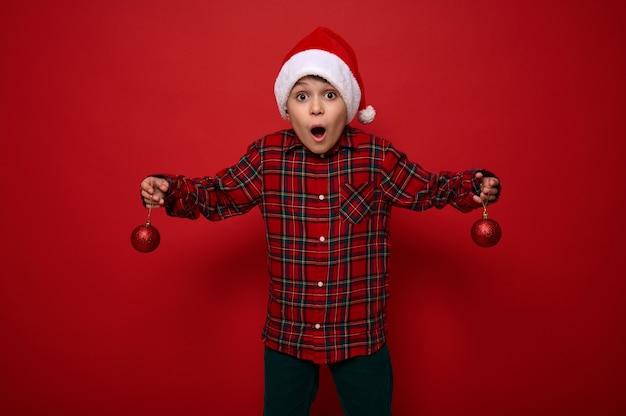 Красивый изумленный малолетний мальчик, удивленный красивый ребенок стоит на красном фоне с рождественскими сферическими блестящими игрушками на руках, с удивлением смотрит в камеру. новогодняя концепция с копией пространства
