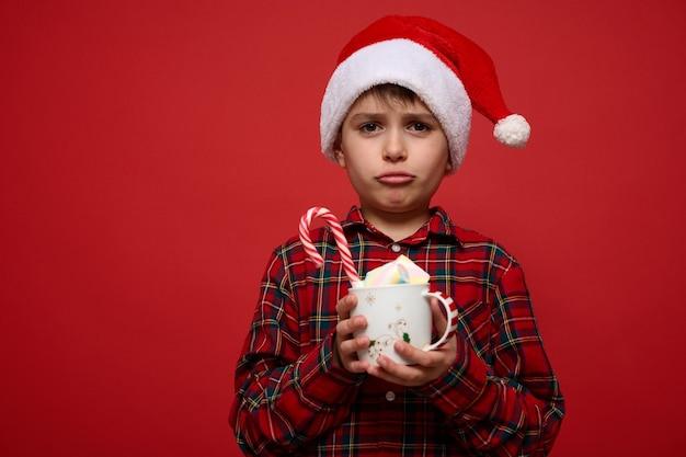 Красивый изумленный расстроенный малолетний мальчик в шляпе санты позирует на красном фоне с кружкой горячего шоколадного напитка с зефиром и полосатой сладкой конфетой. рождественская концепция с копией пространства для рекламы