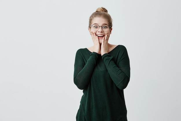 ブロンドの髪の結び目と眼鏡を持つ美しい驚かれる女性は彼女の目を信じることができず、ボーイフレンドからの予期しないプレゼントを受け取ってうれしくて、幸せで驚いた表情を持っています。幸福の概念。