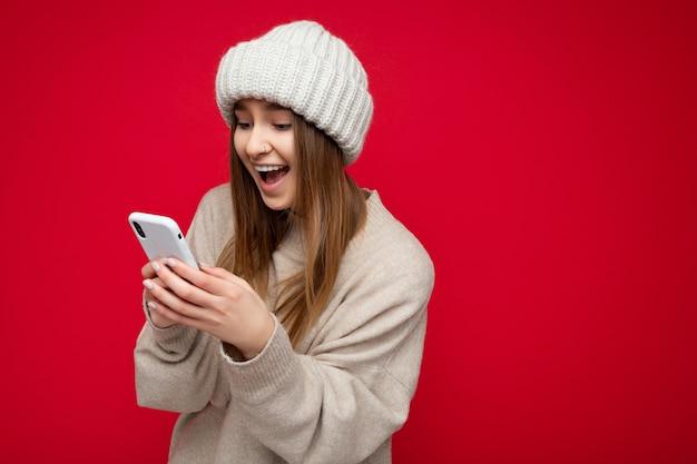 캐주얼 베이지 색 스웨터와 베이지 색 모자를 입고 아름 다운 놀란 젊은 금발의 여자는 빨간색 이상 격리