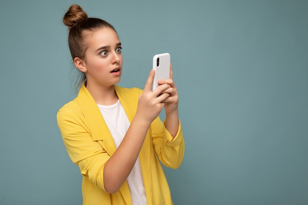 Красивая удивленная молодая девушка в желтой куртке и белой футболке, стоящая изолированно на синем фоне, серфинг в интернете по телефону, глядя на экран мобильного телефона.