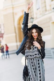 春や秋に長いウェーブのかかった髪型で美しい驚くべきブルネットの女性は、通りを歩いてスタイリッシュな都会の服。赤い唇、スリムなボディ。ストリートファッションのコンセプトです。