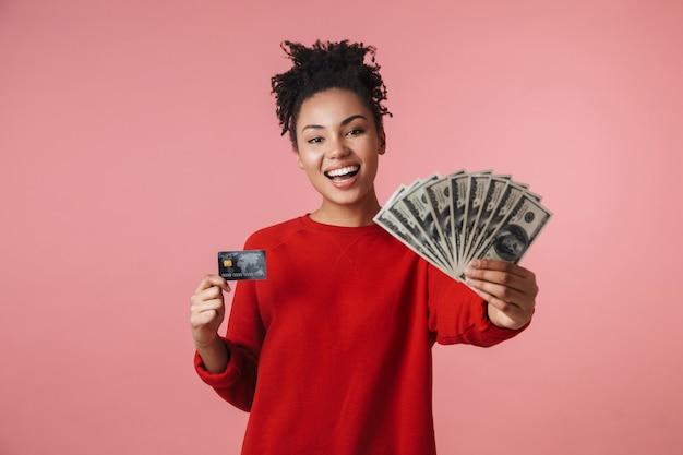 Красивая удивительная счастливая возбужденная молодая африканская женщина позирует изолированной над розовой стеной, держащей деньги и кредитную карту.
